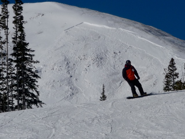 A fracture line is visible on classic convex avalanche from lower Peak 7 terrain, groomed snow in foreground.