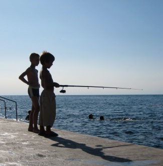 A couple of young Slovenians wet a line in the Adriatic. PHOTO BY LEIGH WADDEN.