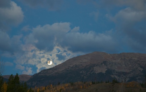Full moon setting Sunday, Sept. 30, over Buffalo Mountain, Summit County, Colorado.