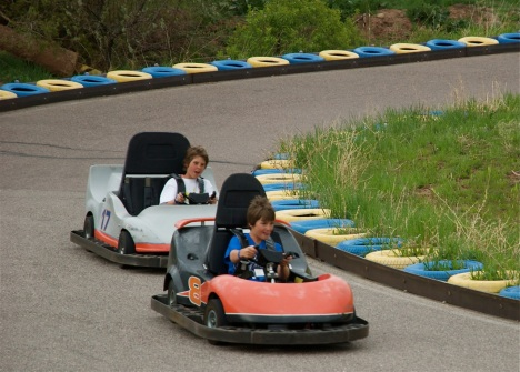 Kids leaning into the curve on the gokart track, Heritage Square, Colorado.