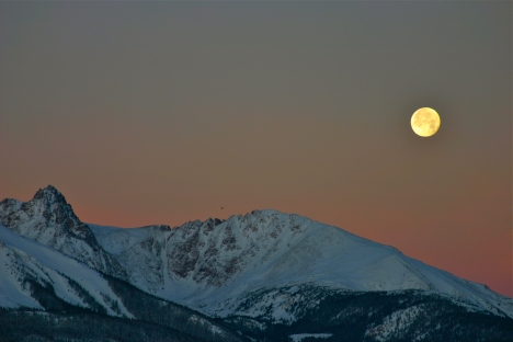 December's full moon sets over the Gore Range in Summit County, Colorado.