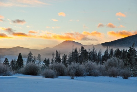 Dawn breaks over snow-covered Summit County, Colorado.
