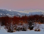 February's full moon rises into the wintry pink sunset glow.