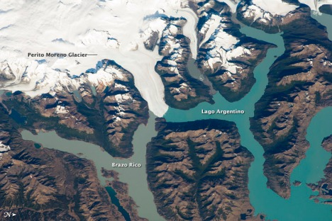 The Perito Moreno Glacier is one of the largest in Patagonia at 30 kilometers long. The glacier descends from the Southern Patagonian Icefield (image top)—2100 meters elevation (6825 feet) in the Andes Mountains—down into the water and warmer altitudes of Lago Argentino at 180 meters above sea level.
