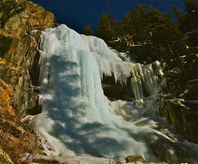 The shadow of tree falls across a frozen waterfall near Frisco, Colorado.
