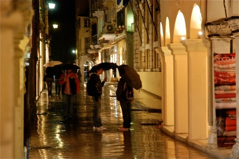 Shoppers stop to chat in downtown Corfu on a rainy evening in the Ionian Sea.