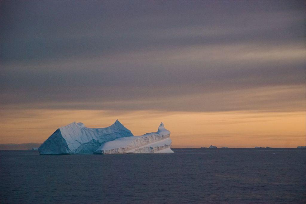 Sunlit icebergs gleam on the horizon in the Antarctic Sound.