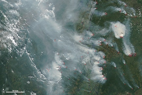 Acquired by MODIS on July 25, 2013, the natural-color image shows smoke billowing from fires in the Khanty-Mansiyskiy and Yamal-Nenetskiy districts. Red outlines indicate hot spots where MODIS detected abnormally warm surface temperatures associated with fire.