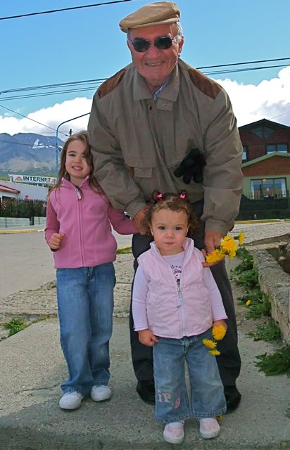 A visibly proud grandpa picks bunches of dandelions with his grandkids in Ushuaia, Argentina.