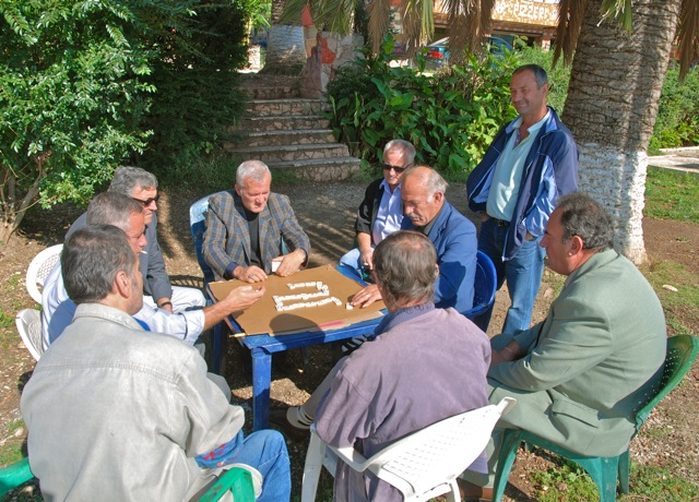 The Saranda police chief (checked jacket) enjoys a game of dominoes with friends along the seaside promenade in Saranda.