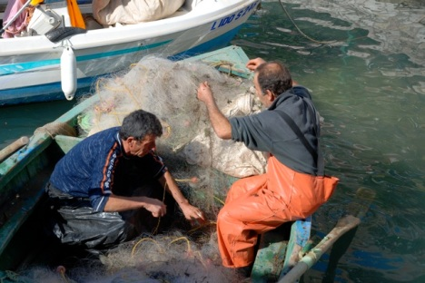 Fishermen in the Saranda harbor tend their nets on a sunny Sunday afternoon.