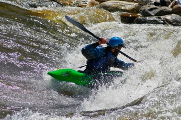 A kayaker charges the wave at the Steamboat Springs whitewater park.