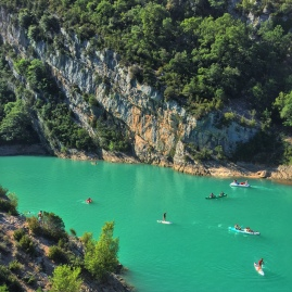 Near the mouth of the gorge, at the Lac de Sainte-Croix,, boaters and stand-up paddlers play in the water.