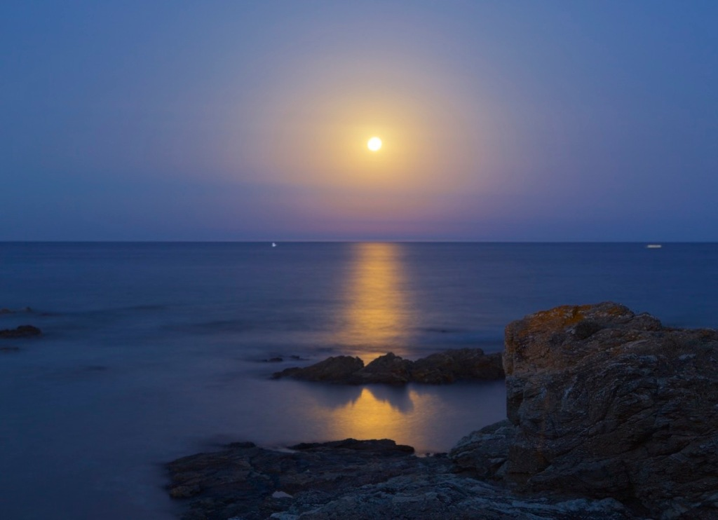 Full moon rising over the Mediterranean in a time exposure.